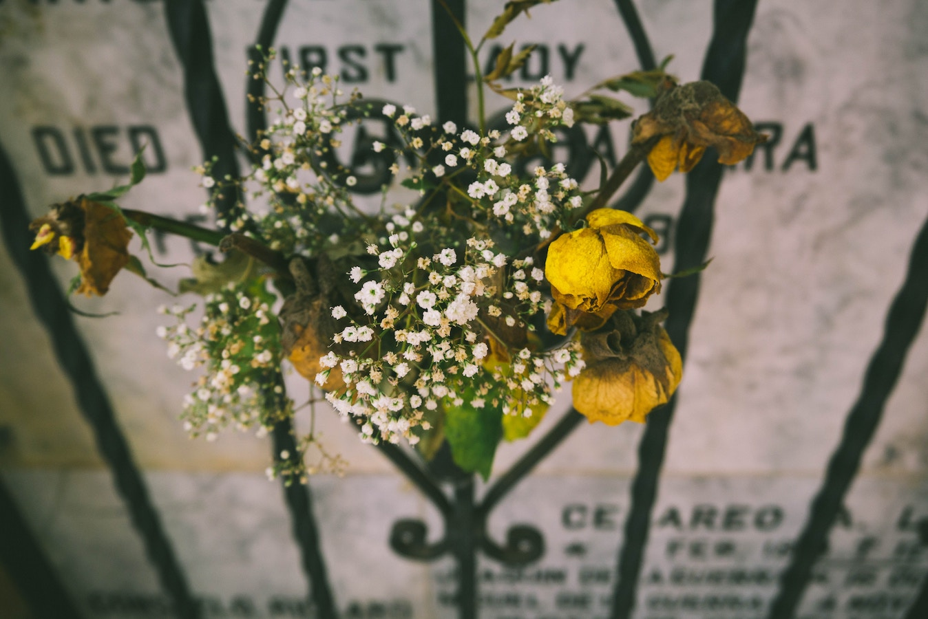Funeral Flowers in front of Gated Headstone - Funeral Loan choices
